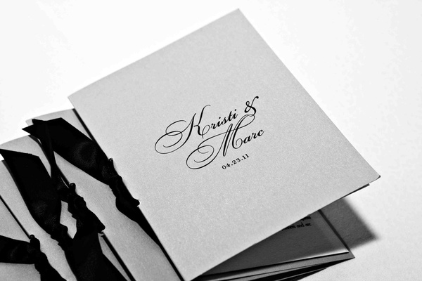 Black and white photo of wedding program with ribbon