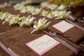 brown suede program covers with pink ribbon and white flower
