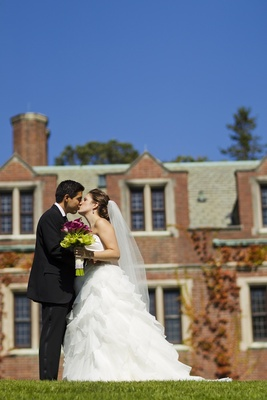 Bride and groom kiss in front of The Mansion at Natirar
