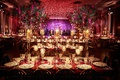 opulent luxury wedding reception trees purple neon sign red candlelight flowers greenery