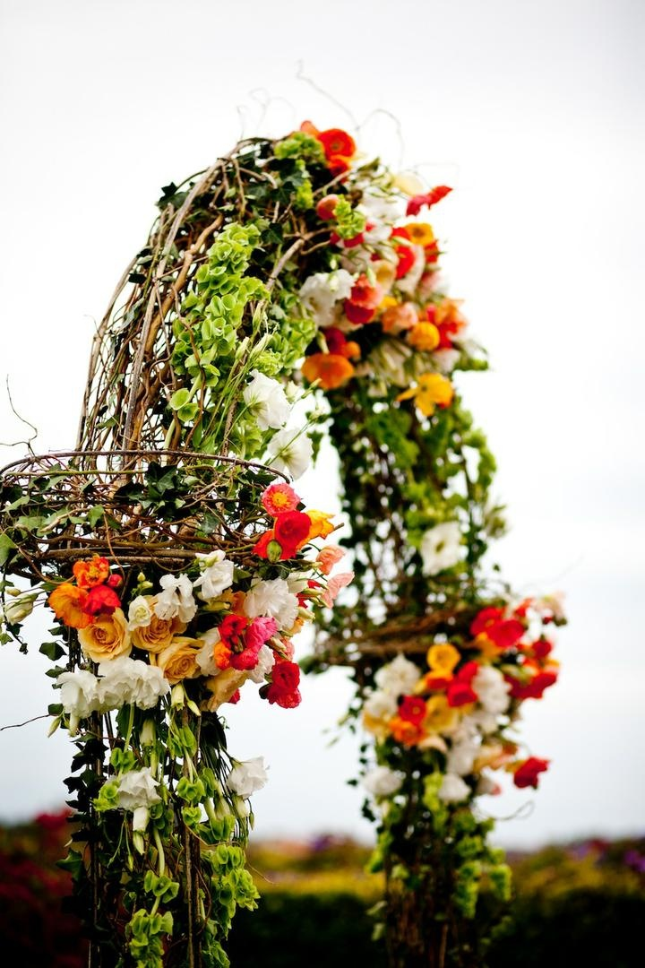 Greenery, branches, and bright roses on wedding flower arch