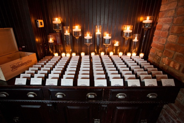 New York wedding reception escort card tents on table desk with candles in back and wood box