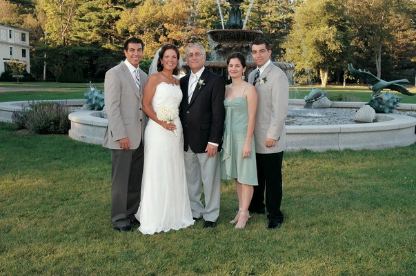 Bride and groom with three wedding guests and family