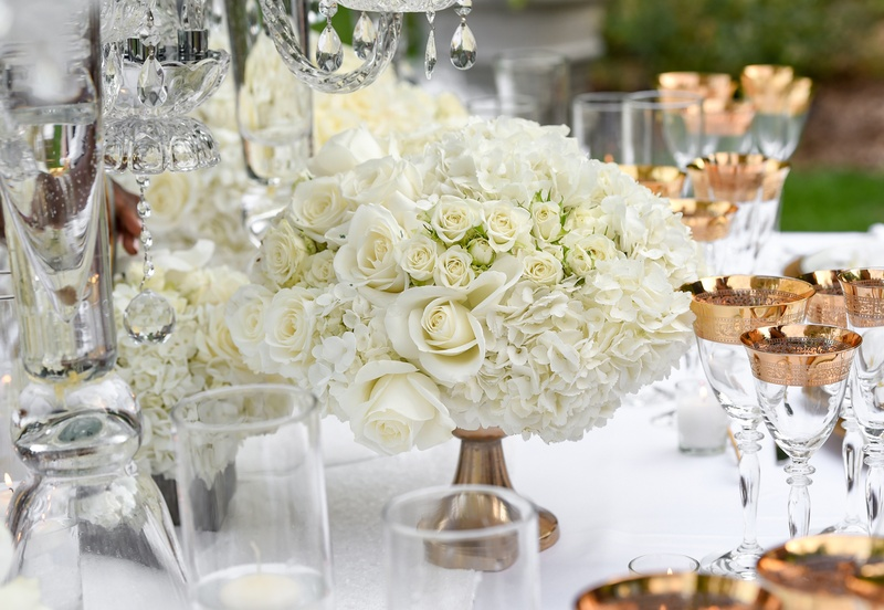 white roses and hydrangeas in small arrangement held by gold base