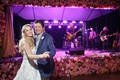 Bride in a strapless Nardos Imam dress dances with groom in blue plaid blazer, Pat Green performs
