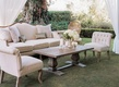 Plush sofa, chair, and wood coffee table on grass at wedding reception