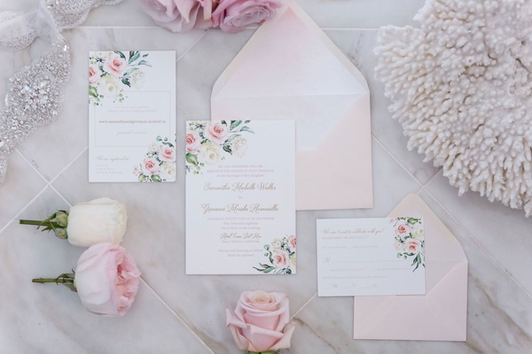 wedding invitation suite light pink blush envelope with white stationery pink flower print in corner