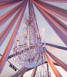 Golden chandeliers with faux taper candles and crystals suspended from clear tent with draping