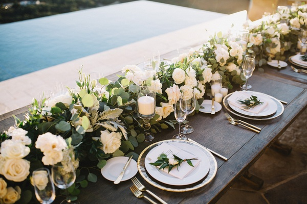 wooden farm table, floral runner with white flowers and greenery