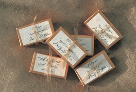 Favors in boxes tied with gold ribbon