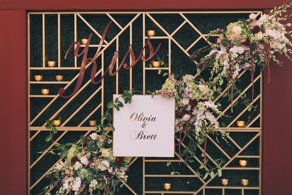wedding photo booth backdrop with burgundy border, gold geometric lines, boxwood hedge, florals