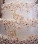 White wedding cake with small sugar flowers with gold centers, sugar butterflies with gold outline