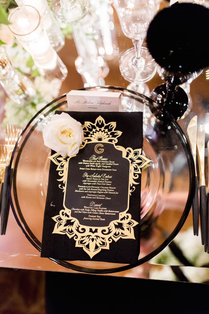 Mirror table black goblet glassware gold menu card monogram fresh flower black gold flatware candles