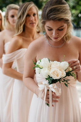 Bridesmaid in a light Amsale dress holds bouquet of white roses and tulips, greenery