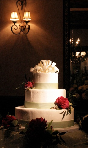 White wedding cake with green bands and red flowers