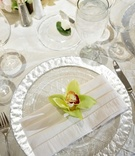 Silver-rimmed charger plate, white napkin, and green orchid