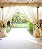 Tented wedding ceremony with large arrangement of white flowers at the entrance