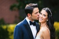 groom in navy blue tuxedo with black bow tie side part kissing bride on cheek smiling