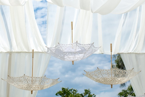 Lace parasols hanging upside down from drapery at outdoor bridal shower