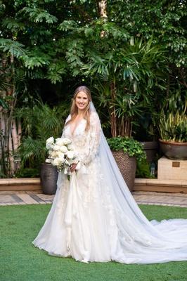 bride in marchesa wedding dress long sleeve winter wedding la white bouquet rose flowers hair down