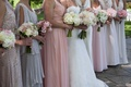 a bride stands with her bridesmaids in varying styles and colors of dresses with different bouquets