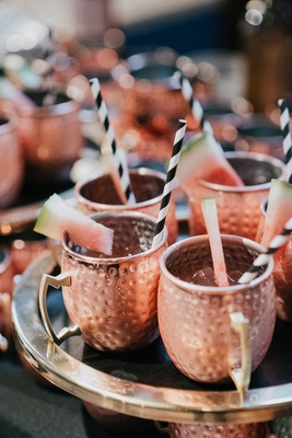 wedding cocktail hour drinks moscow mule copper mug with black white stripe straw watermelon garnish