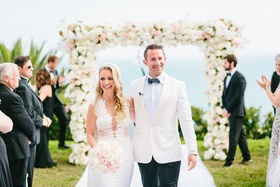 Bride and groom walking up aisle outdoor wedding ceremony guests clapping white pink flowers