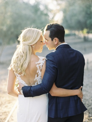 bride in pronovias wedding dress, groom in blue windowpane suit jacket, bride and groom from back