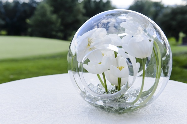 White tulips inside glass globe orb decoration at wedding
