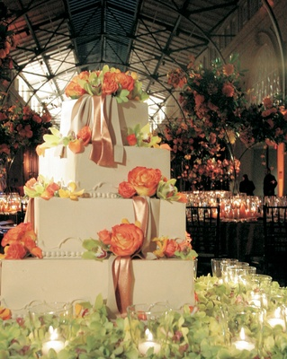 Four-tiered wedding cake with roses, orchids, and ribbons