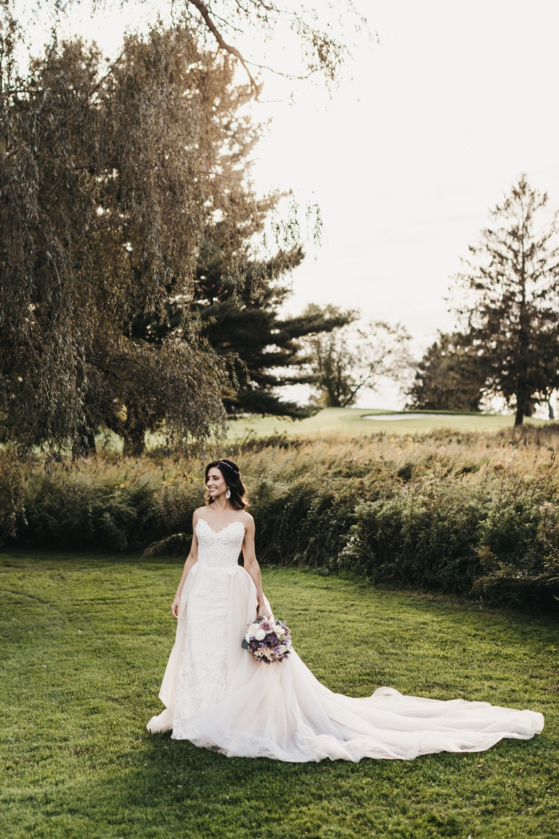 bride in nicole spose wedding dress with long train standing in a green field