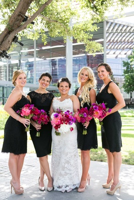 a bride in lace gown with bridesmaids in assorted black cocktail dresses bright pink purple bouquets