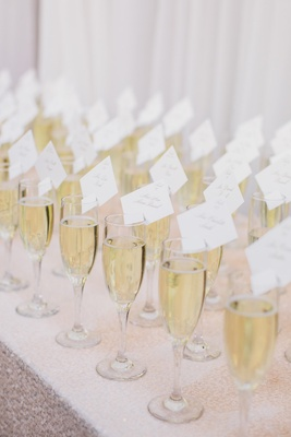 Escort cards place settings on champagne flutes filled with bubbly