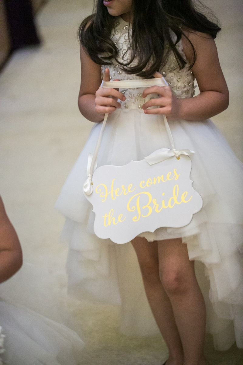 "older flower girl in high-low dress carrying a ""here comes the bride"" sign"