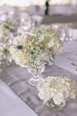 Small glass urn filled with blue thistles and lace
