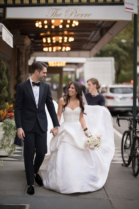 Bride in strapless monique lhuillier wedding dress groom in tuxedo outside of the pierre in new york
