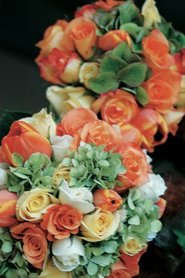 flower bouquets of orange, yellow and white roses and green hydrangea