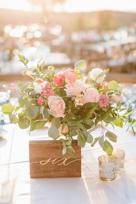 outdoor wedding reception table number wood block with gold calligraphy number next to pink flowers