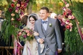 Bride in a Claire Pettibone dress with gold and silver embroidery, veil with groom in grey suit