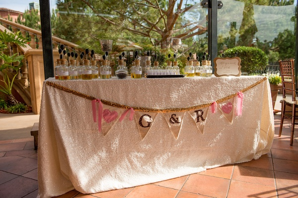 Wedding shower perfume station with banner of couple's initials and hearts on triangle flags