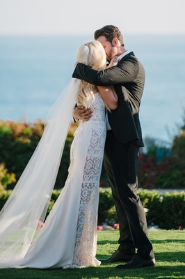 Groom in black tux kisses bride in a Galia Lahav dress with lace panels, veil at ceremony
