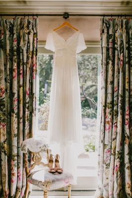 wedding dress hanging up in window with sleeves and velvet peep toe heels pink