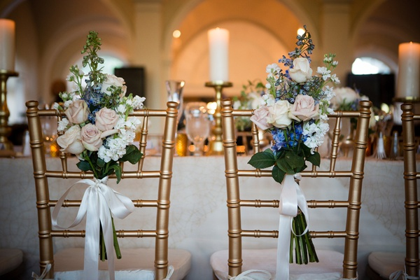 gold chiavari chairs with bouquet tied on back