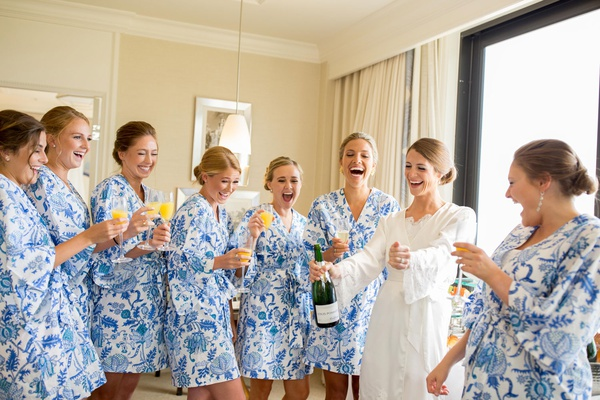 bride in white robe, bridesmaids in blue-and-white floral robes, mimosas while getting ready