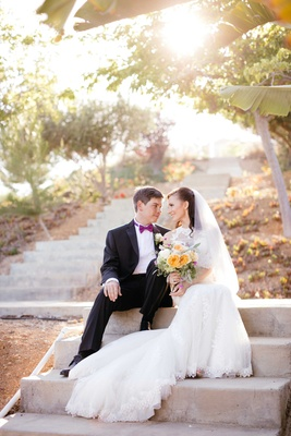 bride and groom sit on steps of venue and look at each other