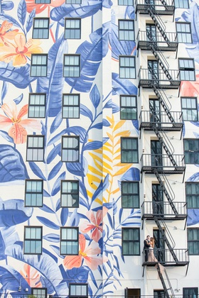 wedding portrait in downtown los angeles on fire escape of building tropical flower leaf mural