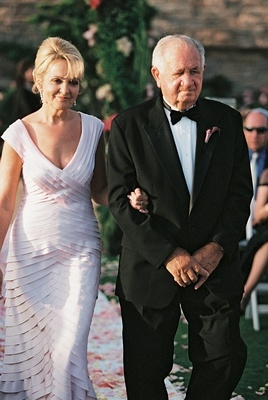 mother and father of the groom walk down aisle