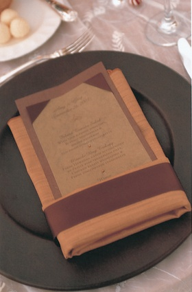 orange napkin holds brown menu card