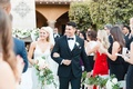 Bride in v neck wedding dress groom in tuxedo bow tie holding bouquet courtyard outdoor ceremony