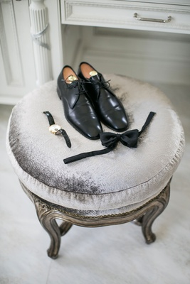 Groom's shoes watch bow tie on stool before ceremony